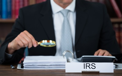 irs agent holding magnifying glass